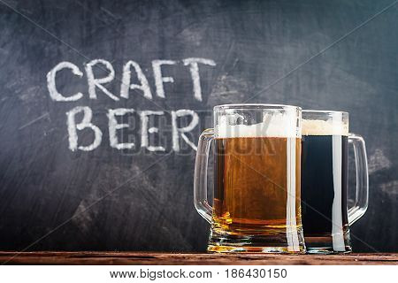 Glasses of light and dark beer on a chalk board background