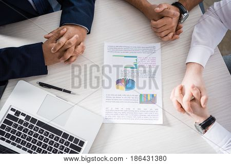 Top Partial View Of Professional Businessmen Discussing Charts At Workplace