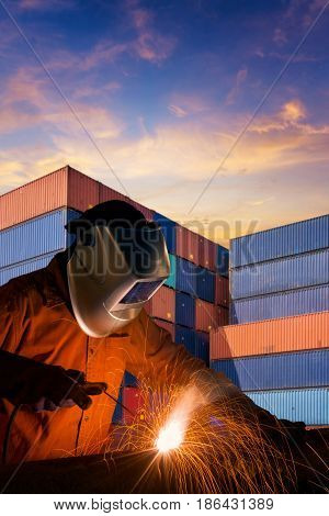 Industrial Welding Worker Welding Steel Structure With Cargo Container Stack In Background For Trans