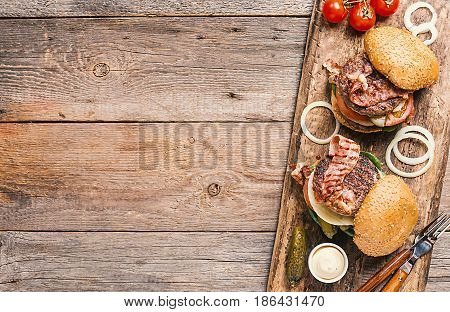 Two fresh homemade burgers on cutting board, pickles, sauce and sliced onion over wooden background. Top view, copy space