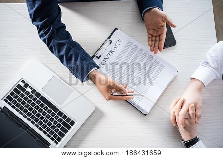 Top Partial View Of Businessmen Discussing Contract At Workplace