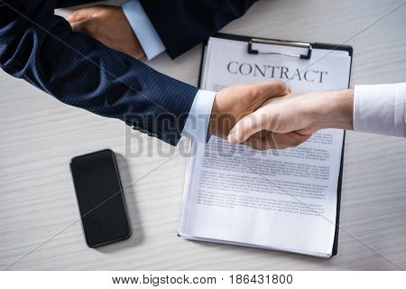 Top Partial View Of Businessmen Shaking Hands With Contract On Table