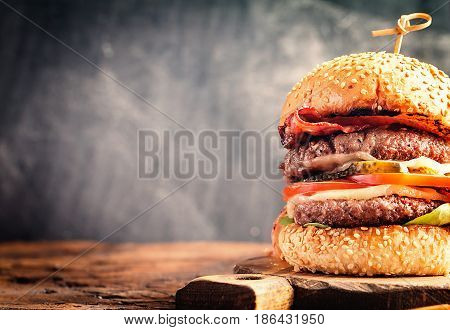 Close up of delicious fresh homemade burger on a wooden table with chalk board background