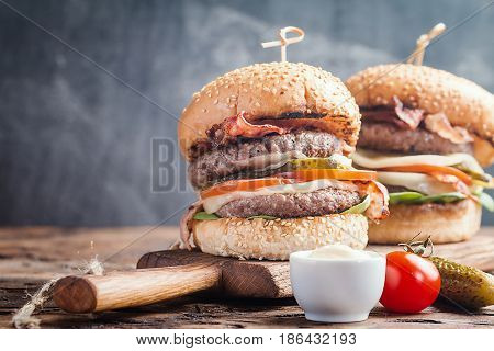 Close up of two delicious fresh homemade burgers on a wooden table with chalk board background