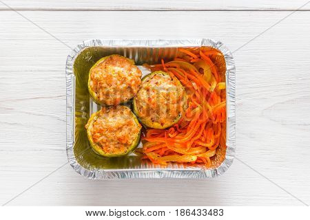 Healthy food delivery top view, diet concept. Take away of fitness meal. Weight loss lunch in foil boxes. Stuffed zucchini and carrot salad on white wood