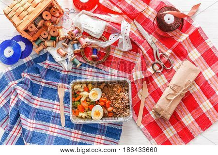 Lunch box healthy food delivery for dressmaker. Flat lay shot of foil container with diet meal for fashion designer at workplace. Healthy nutrition, brown rice, vegetables