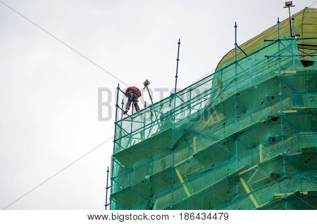 Reconstruction of the building. Working climber at the top restores the old structure. Dangerous job of installers architecture.