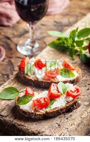 Close up of crostini appetizers with cherry tomatoes, basil, and cheese on cutting board