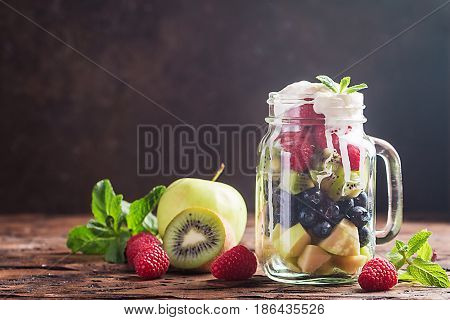 Colorful fruit salad with cream in a jar on wooden background