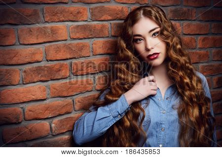 Close-up portrait of an attractive girl with long curly hair standing by the brick wall. Youth fashion, beauty. Long hair, haircare.