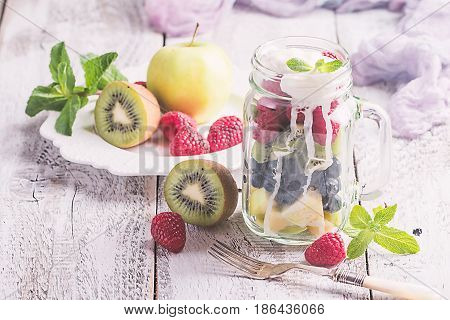 Colorful fruit salad with cream in a jar on white wooden background