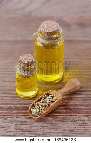fennel essential oil bottles and a wooden scoop with fennel seeds, selective focus, on wooden background