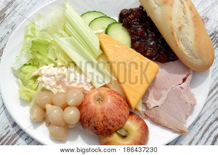 Ploughman`s salad with cheese, ham, coleslaw, pickle, lettuce, celery, apple and a white roll