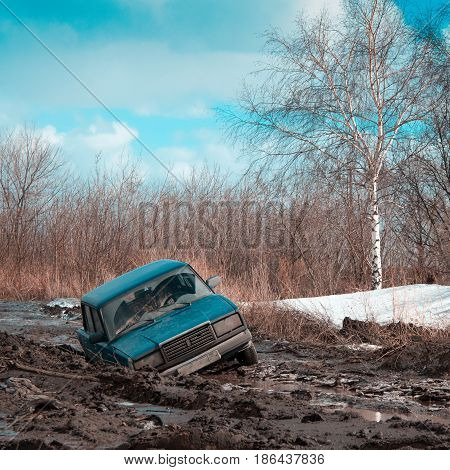 Stuck in dirt and abandoned car on a sunny spring day