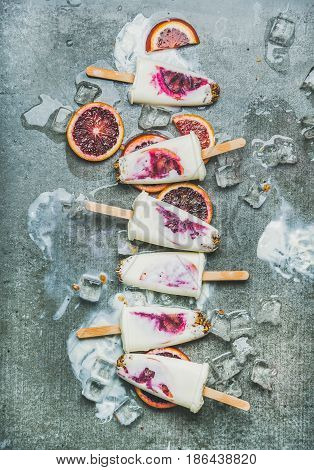 Healthy summer dessert. Blood orange, yogurt and granola popsicles on ice cubes over grey concrete background, top view, vertical composition. Clean eating, dieting, weight loss concept