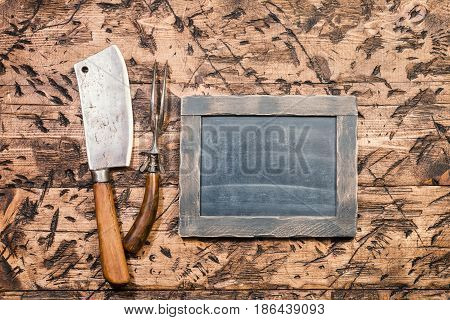 Vintage Meat cleaver, fork and chalk board on old wooden background