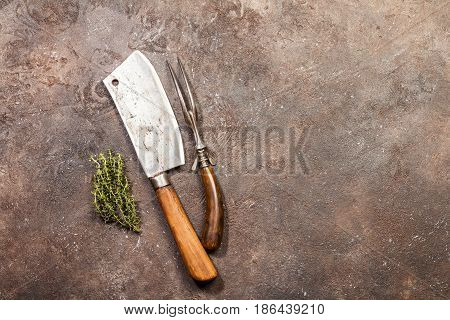 Vintage Meat cleaver and fork on dark brown stone background