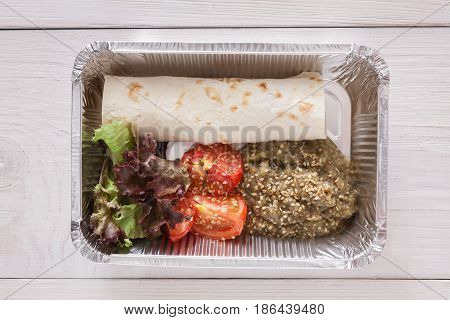 Healthy food, diet top view. Lunch box with Weight loss nutrition closeup. Flatbread roll and tomatoes