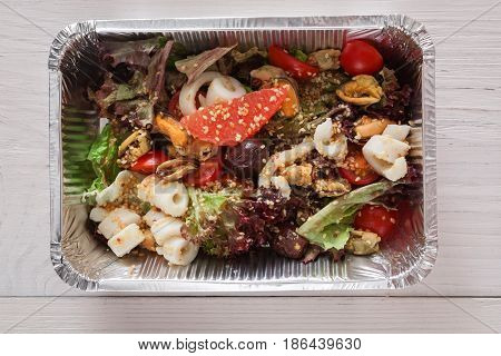 Healthy food, diet top view. Lunch box with Weight loss nutrition closeup. Seafood salad mix