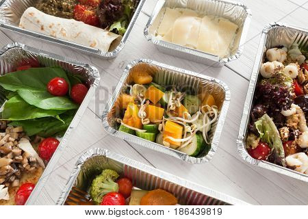 Healthy food background. Take away of natural organic creative meals in foil boxes. Fitness nutrition, fish, colorful vegetable salads and fruits. Top view, flat lay.