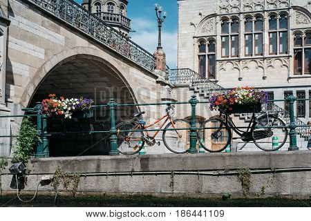 Ghent Belgium - July 31 2016: Canal in the historic center of Ghent with picturesque old buildings and bicycles parked in waterside