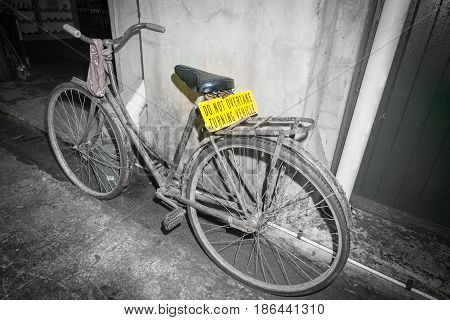 Dirty old pushbike leaning against wall in back street scene with bright yellow sign Do not overtake turning vehicle