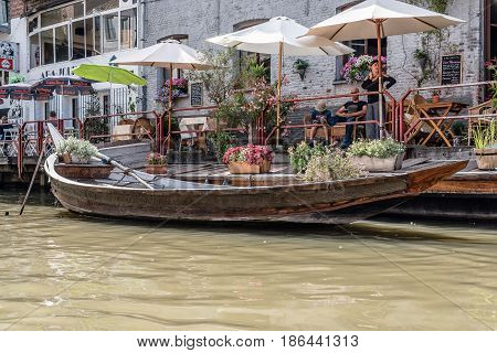 Ghent Belgium - July 31 2016: People sitting on a restaurant terrace ny a canal in the historic center of Ghent with picturesque old boat decorated with flowers