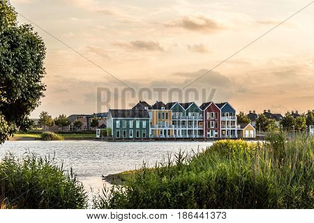 Colorful row houses in Houten Netherlands at dusk and reflections on water.