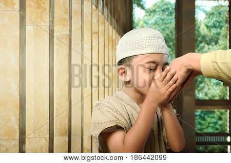 Asian muslim kid kissing his parent hand as respect symbol in the mosque