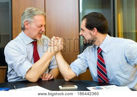 Arm wrestling between businessmen
