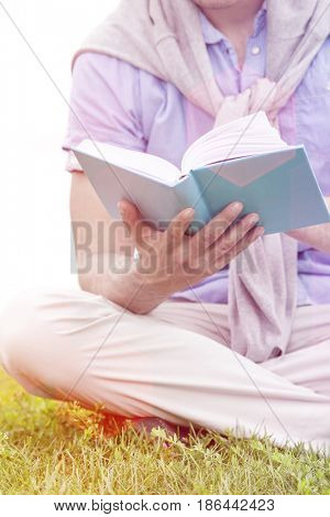 Midsection of man holding book in park