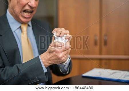 Angry man destroying a document