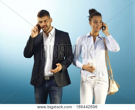 Young couple talking on mobilephone while walking on the way to work.