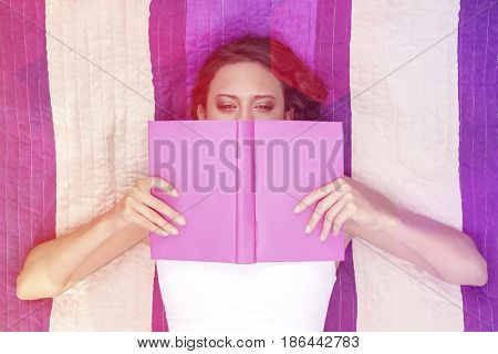 Directly above shot of woman covering face with book while lying on striped picnic blanket
