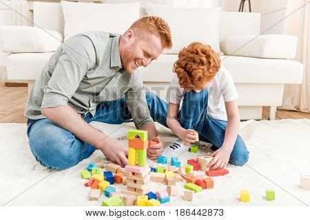Father And Adorable Son Playing With Constructor On Floor At Home, Family Fun At Home Concept