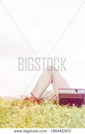 Midsection of man lying by vintage radio on grass against clear sky