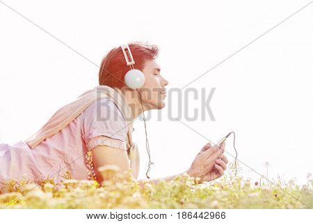 Side view of man enjoying music on MP3 player using headphones in park against clear sky