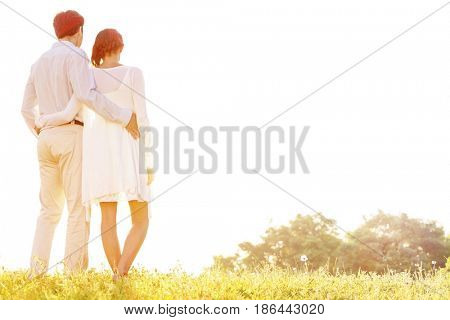 Rear view of loving couple standing arms around against clear sky