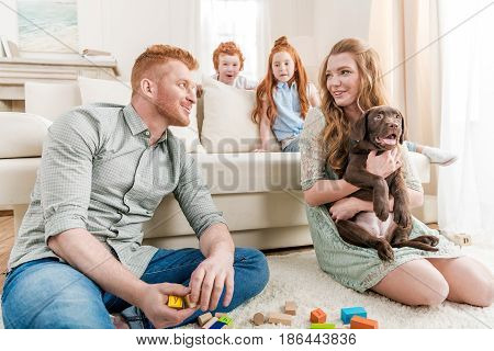 Beautiful Redhead Family With Puppy Playing With Constructor On Floor At Home, Family Fun At Home Co