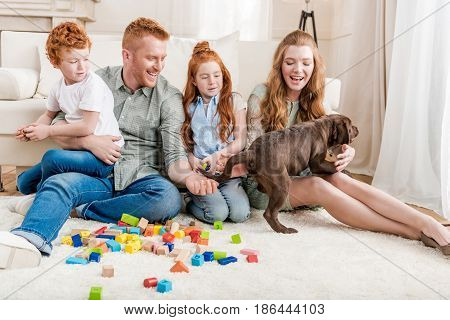 beautiful redhead family with puppy playing with constructor on floor at home family fun at home concept