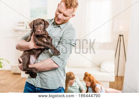 father holding labrador retriever puppy happy family behind at home family fun at home concept