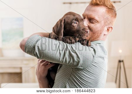 Happy Redhead Man Holding Labrador Retriever Puppy At Home