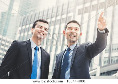 Two businessmen standing outdoors in the city with one hand pointing out - business partner and co-worker concepts