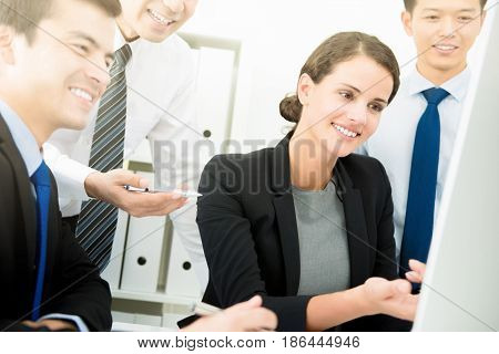 Business people looking at computer screen discussing work