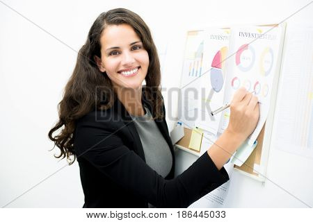 Smiling businesswoman writing on document at noticeboard