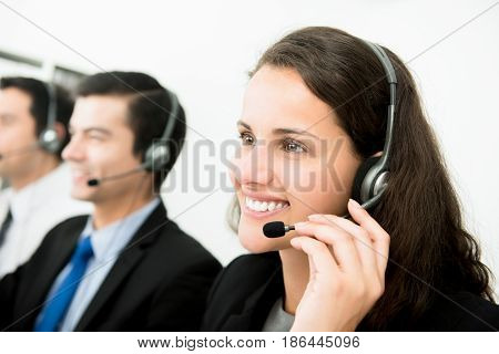 Beautiful smiling woman working in call center as an operator or telemarketer