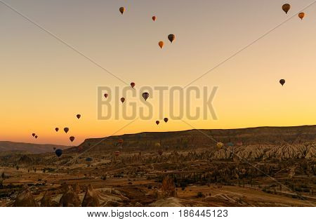 Hot air balloons flying over valley of Cappadocia at sunrise. Nevsehir Province. Turkey