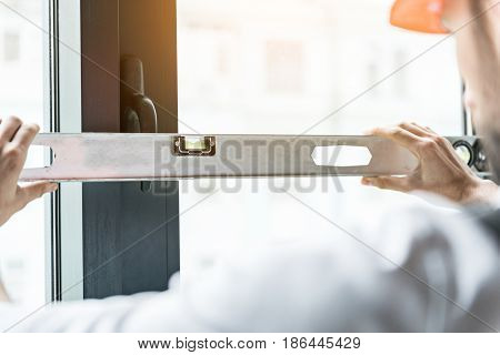 Builder in helmet checking angle of deviation on window frame. He holding building level near handle. Close up of his hands