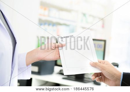 Customer (patient) giving prescription to pharmacist in pharmacy