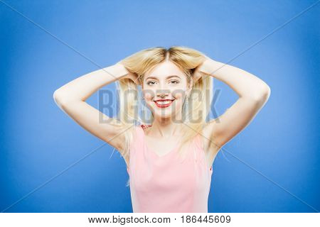 Portrait of Playful Smiling Blonde in Pink Dress on Blue Background. Amazing Pretty Woman with Long Hair is Having Fun Posing in Studio.